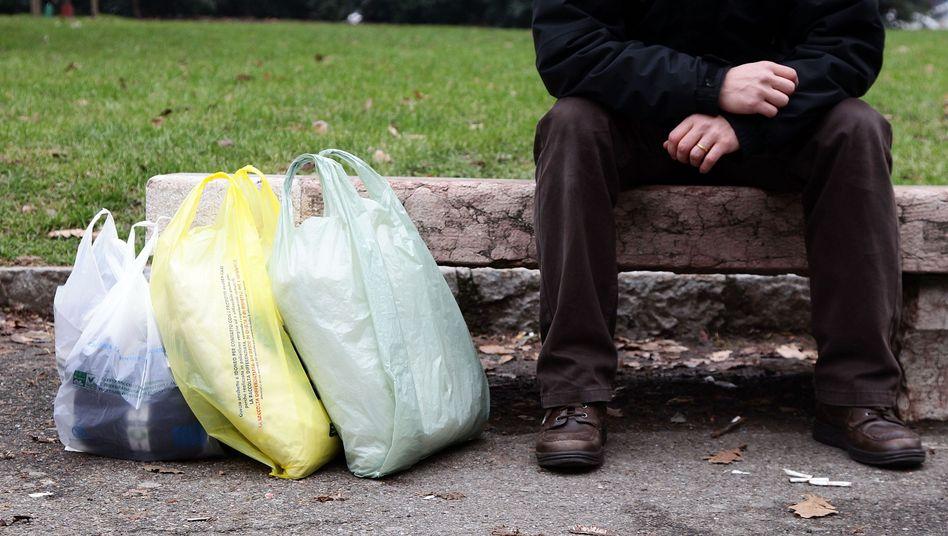 Mann mit Plastiktüten: Praktisch für den Menschen, ein Graus für die Umwelt