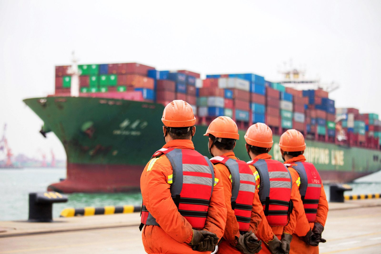 QINGDAO, CHINA - NOVEMBER 08: Workers wait to unload shipping containers at Qingdao Port on November 8, 2018 in Qingdao