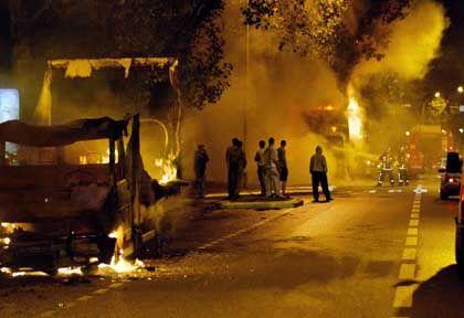 Local youths watch as firemen extinguish burning vehicles in Paris last week.