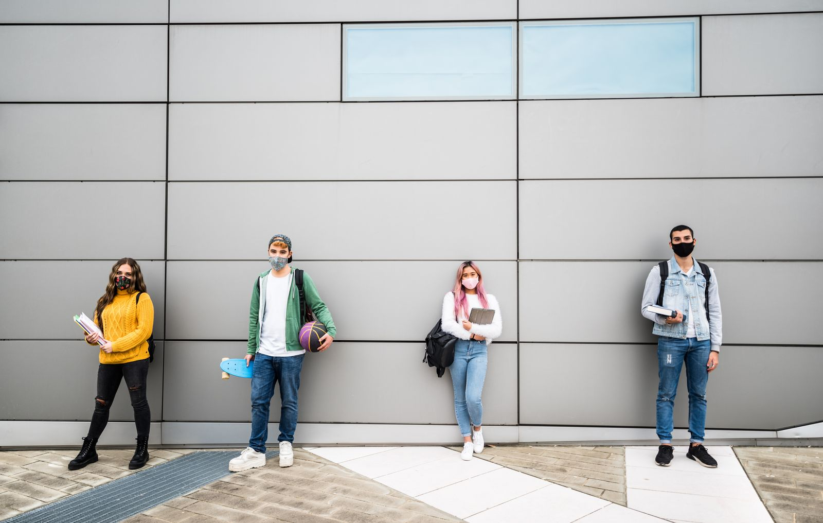 Young students with face mask in casual clothes standing in front of a grey wall background - New normal concept with people going to school