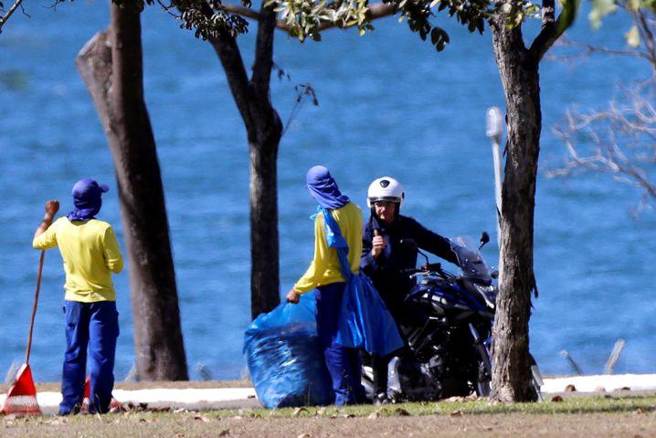 """Jair Bolsonaro auf seinem Motorrad auf dem Gelände der Präsidentenresidenz """"Palácio da Alvorada"""": Trotz Corona-Infektion unterhält er sich ohne Maske mit Angestellten"""