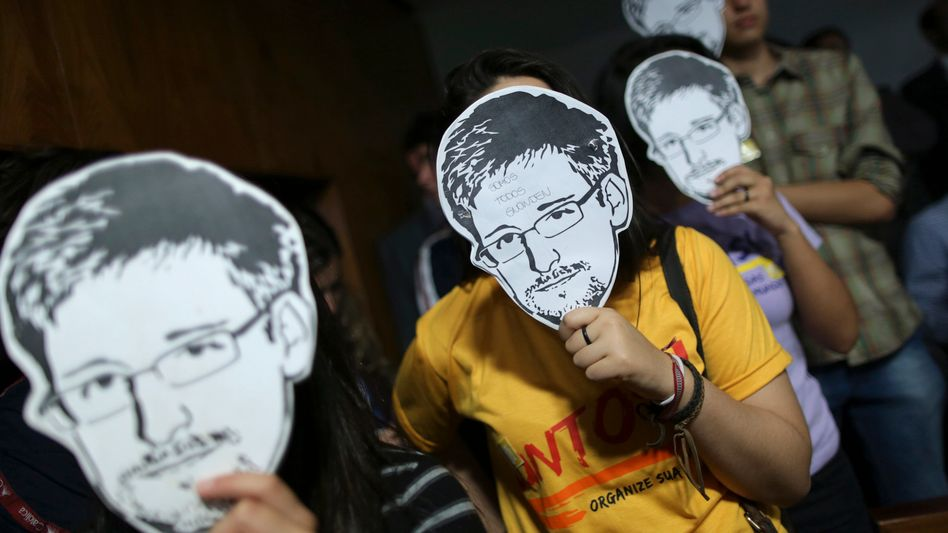 Protesters carry masks of Edward Snowden during a protest in Brazil.