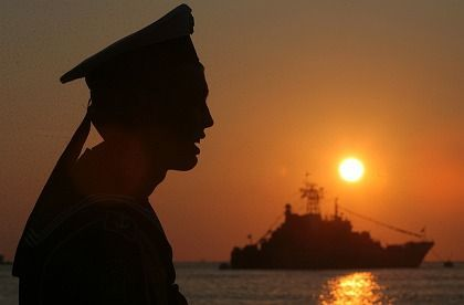 A sailor looks out at a Russian warship stationed at the Crimean port of Sevastopol.