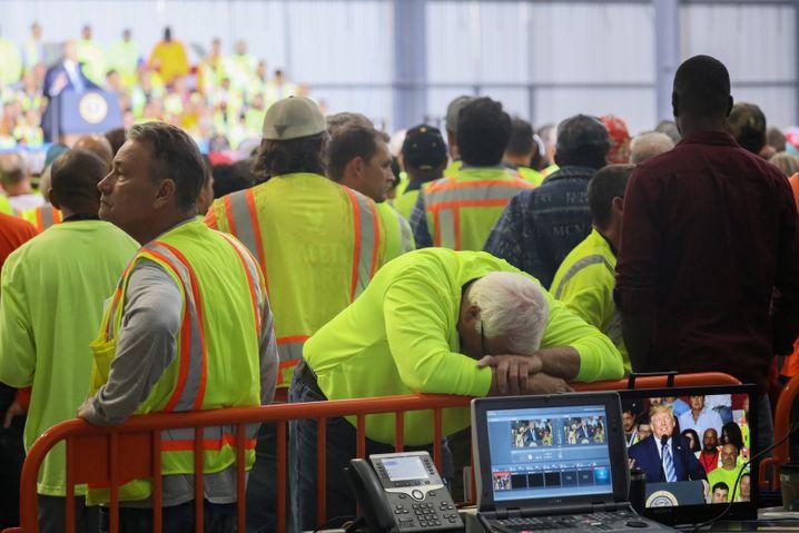 Geste des Protests oder einfach müde: Ein Arbeiter stützt seinen Kopf auf ein Absperrgitter, während Trump spricht