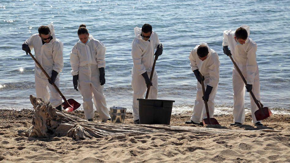 Feuerwehrleute und Mitglieder des Zivilschutzes reinigen den Strand von Scaffa Rossa in Solaro