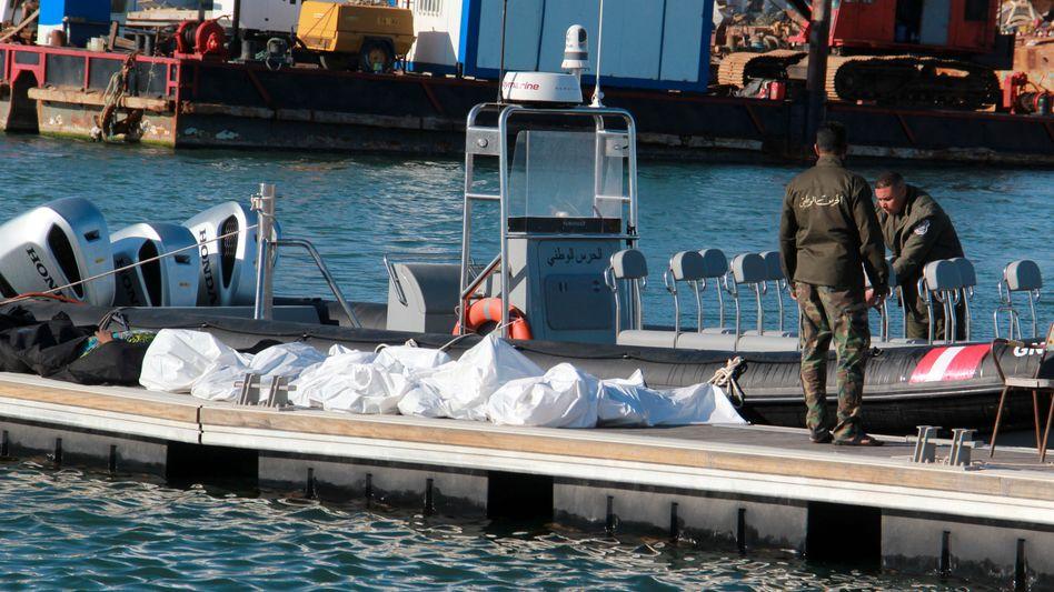 Einsatzkräfte stehen im Hafen von Sfax neben den zugedeckten Leichen der Opfer eines Bootsunglücks