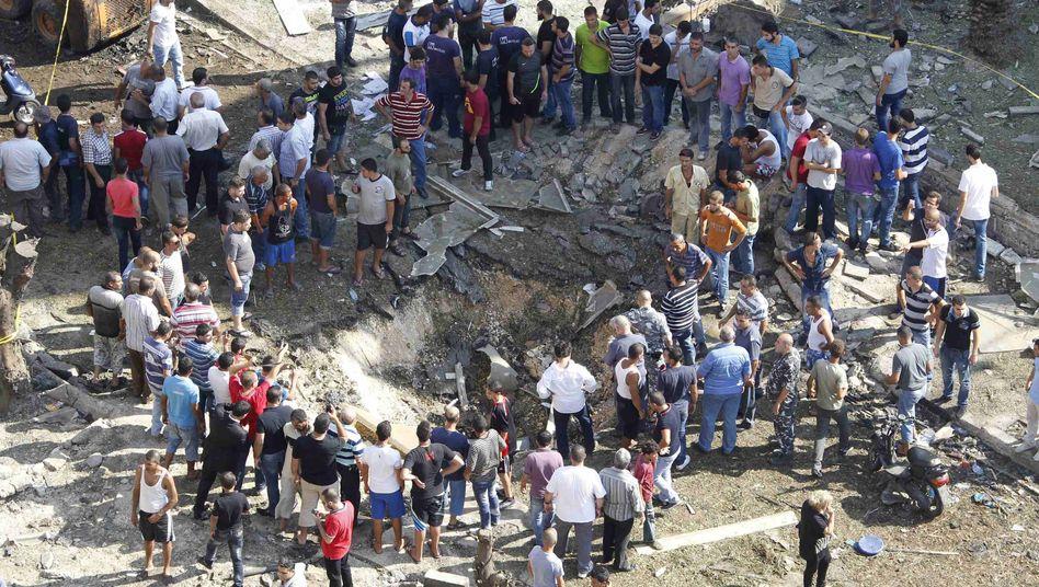Tripoli: Anwohner vor einem der Krater, der durch die Explosion entstand