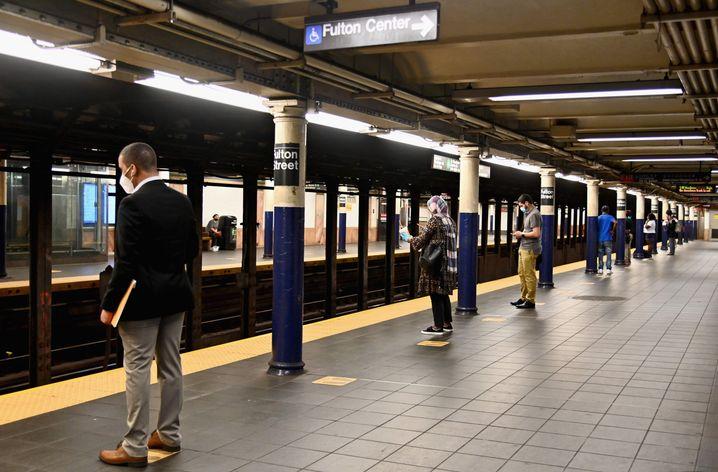 Pendler mit Schutzmasken warten in Manhattan, New York, auf die U-Bahn. Wegen der Coronakrise sind die Fahrgastzahlen stark gesunken