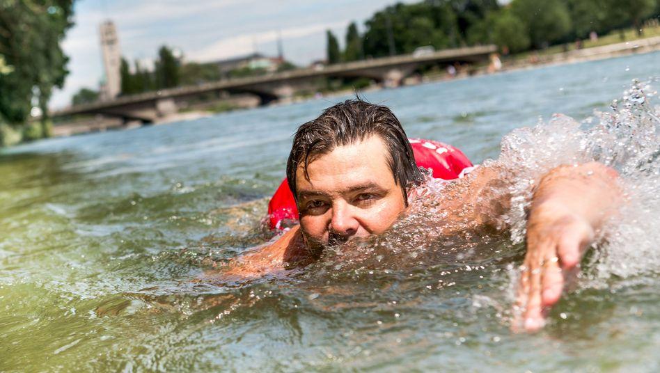 Benjamin David schwimmt in der Isar in München
