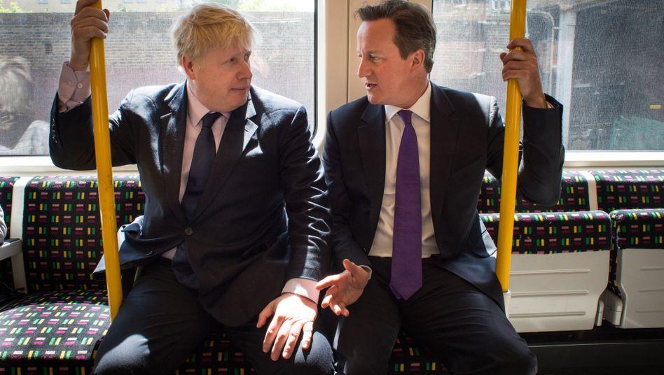 Premierminister Boris Johnson (l.) und sein Vorgänger David Cameron in der Londoner U-Bahn (Archiv)
