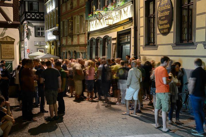 Junge Menschen genießen am 08.06.2014 in der Sandstraße in der Bamberger Altstadt (Bayern) nach Sonnenuntergang kühlende Getränke vor einer Kneipe. Foto: David Ebener/dpa +++(c) dpa - Bildfunk+++ | Verwendung weltweit