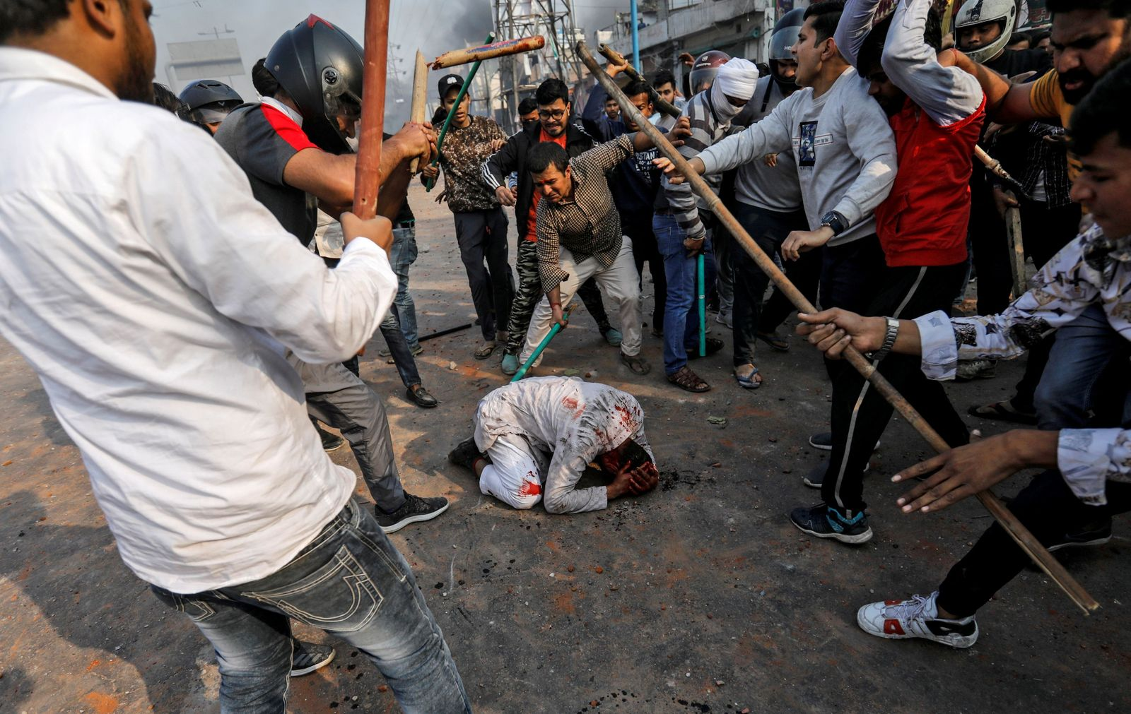 People supporting the new citizenship law beat a Muslim man during a clash with those opposing the law in New Delhi