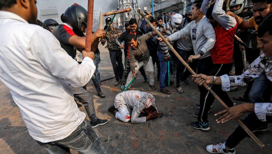 Eine Gruppe Männer schlägt mit Stöcken und Kricketschlägern auf einen am Boden liegenden Muslim ein