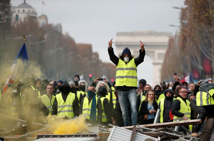 A protester wearing yellow vest, a symbol of a French drivers' protest against higher fuel prices, gestures during clashes on the Champs-Elysees in Paris, France, November 24, 2018. REUTERS/Benoit Tessier - RC1347DBBD20