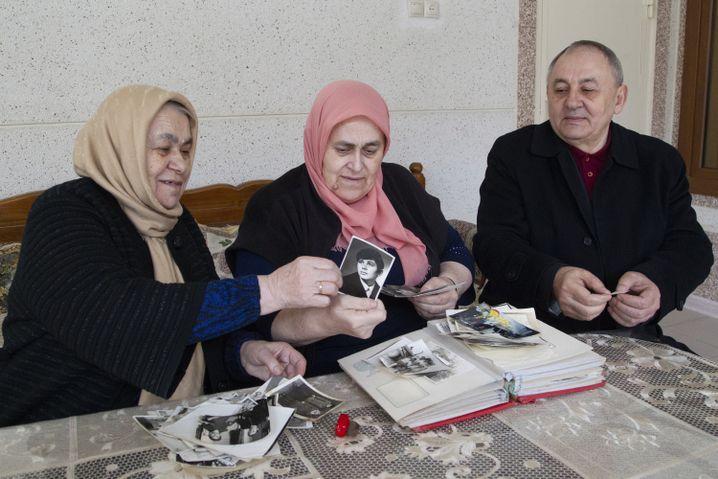 Noch in Kurtschaloj lebende Familienmitglieder zeigen Fotos von Titijew
