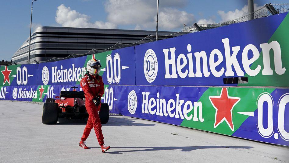 Sebastian Vettel tritt ab. Im Hintergrund sein defekter Ferrari