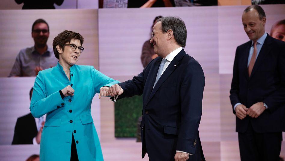 Der neue CDU-Vorsitzende Armin Laschet nimmt Corona-konforme Glückwünsche von seiner Vorgängerin Annegret Kramp-Karrenbauer entgegen