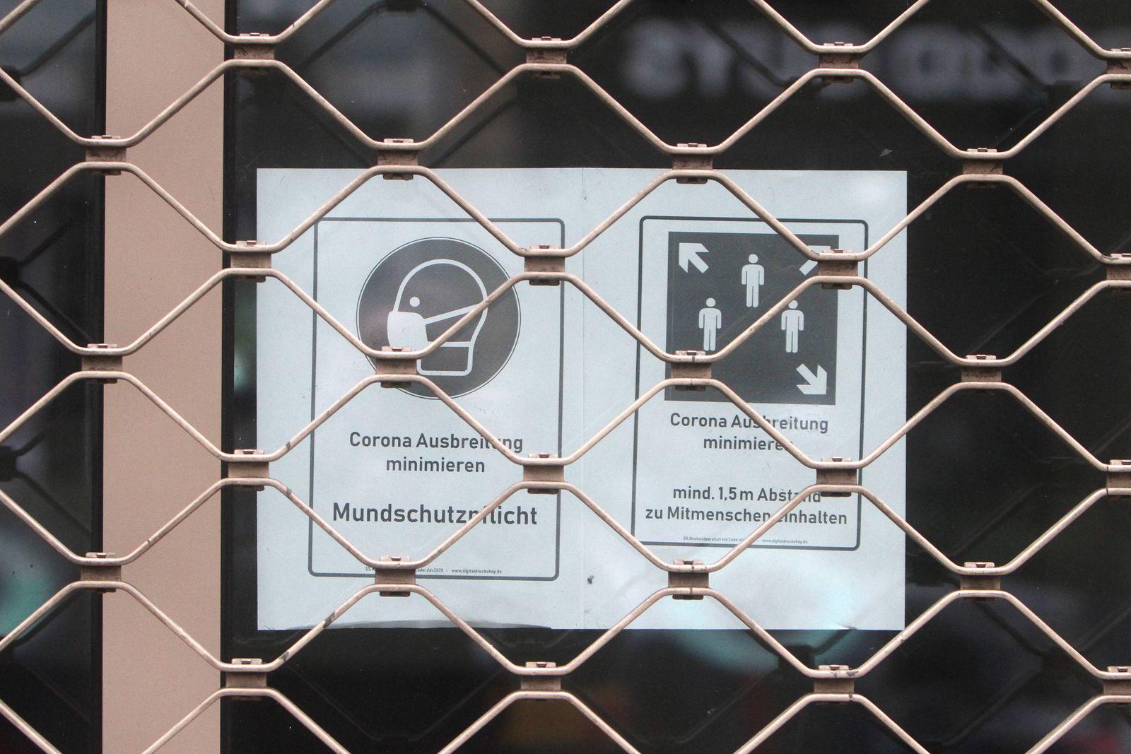 Schild mit Piktogramm Mundschutzpflicht und Mindestabstand klebt im Schaufenster eines mit Rolltor geschlossenen Geschä