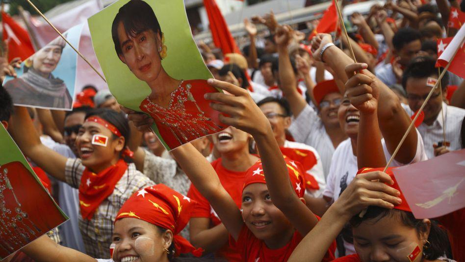 Anhänger der Oppositionspartei mit Bildern von Suu Kyi: Sieg eindeutiger als erwartet