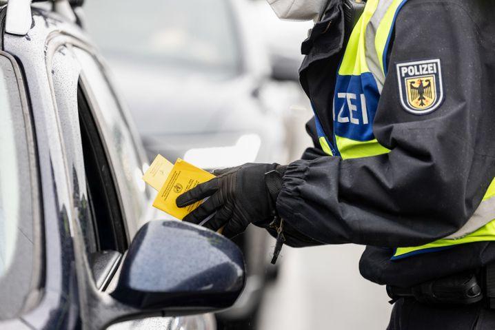Deutscher Bundespolizist kontrolliert an der Grenze zu Österreich auf der A93 Impfpässe