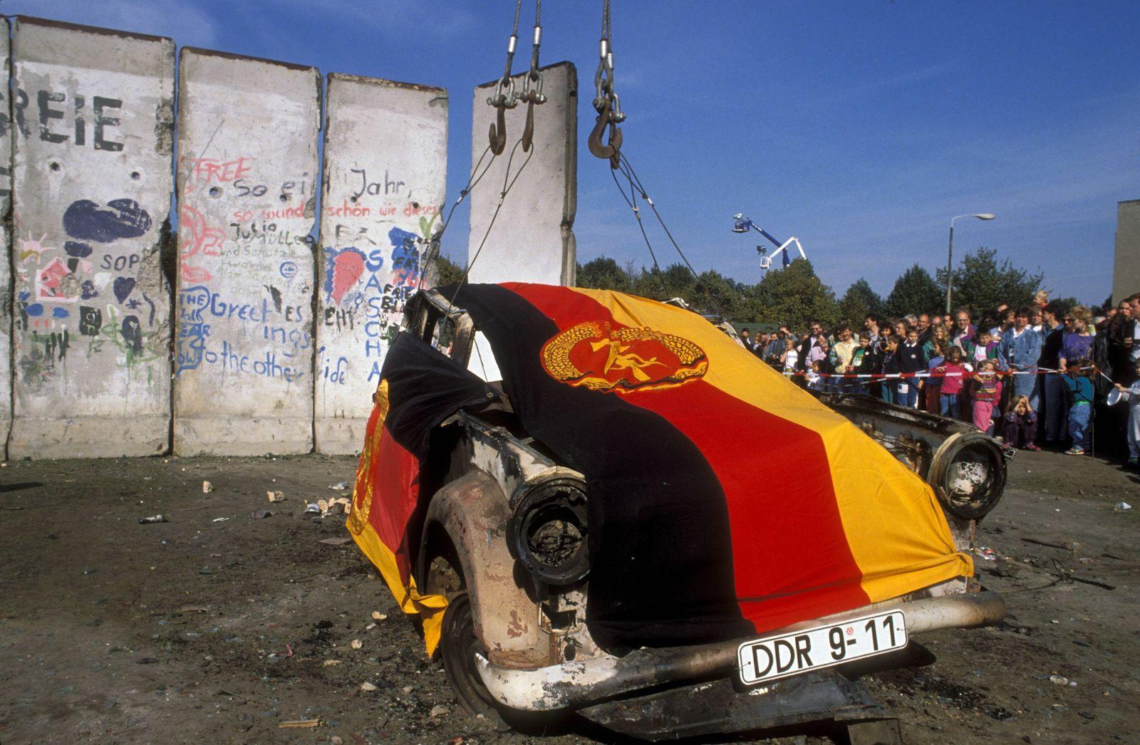 POLITIK 25 Jahre Deutsche Einheit Die Wiedervereinigung Verkohltes Wrack eines Trabanten geschmückt