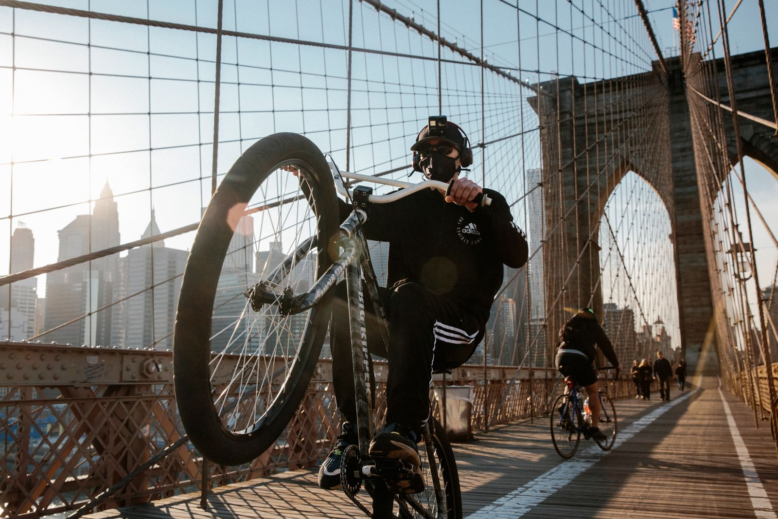 A cyclist pops a wheelie on the Brooklyn Bridge in New York, March 26, 2020. (Mark Abramson/The New York Times)