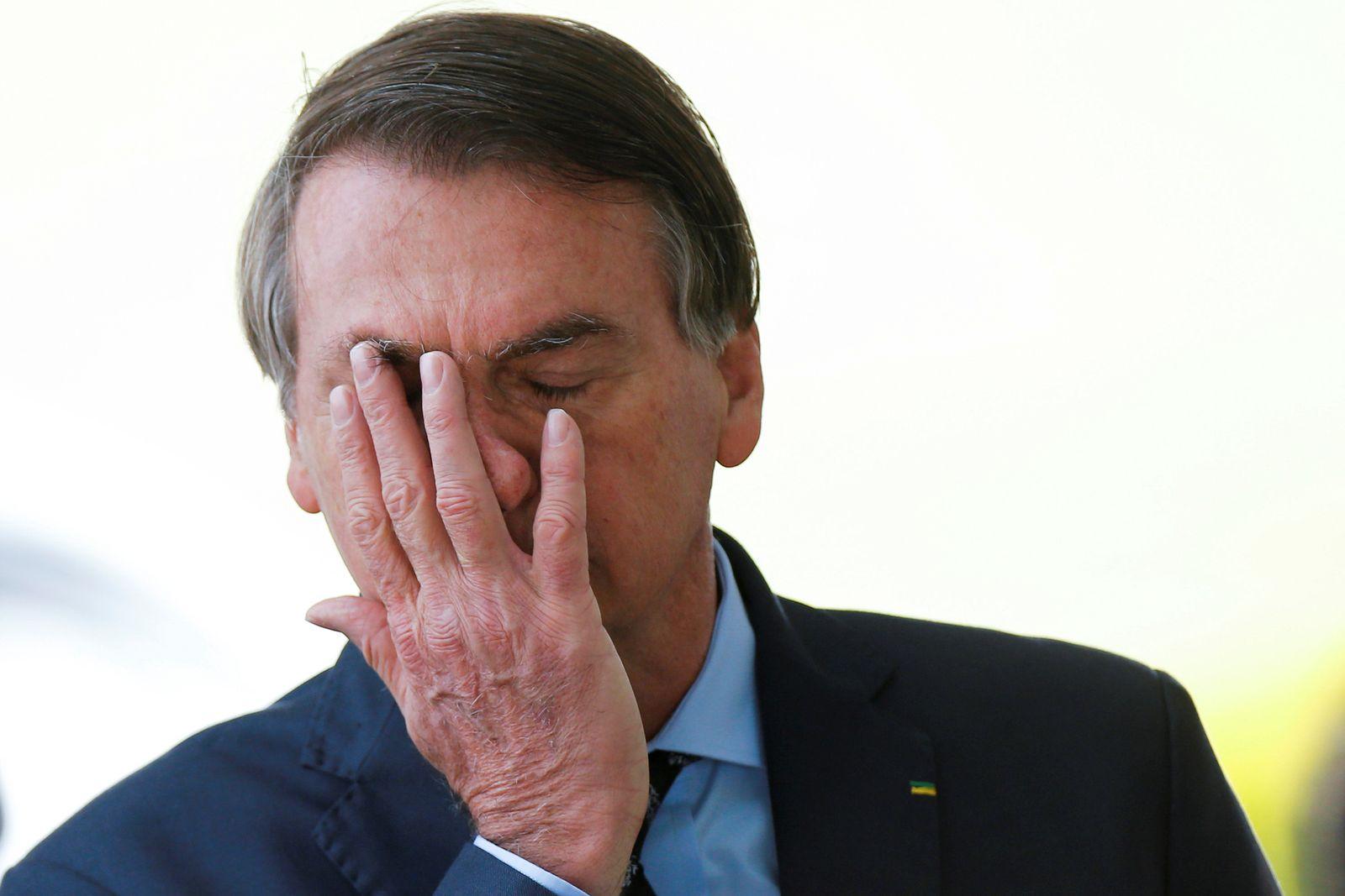 Brazil's President Jair Bolsonaro reacts while meeting supporters as he leaves Alvorada Palace, amid the coronavirus disease (COVID-19) outbreak, in Brasilia
