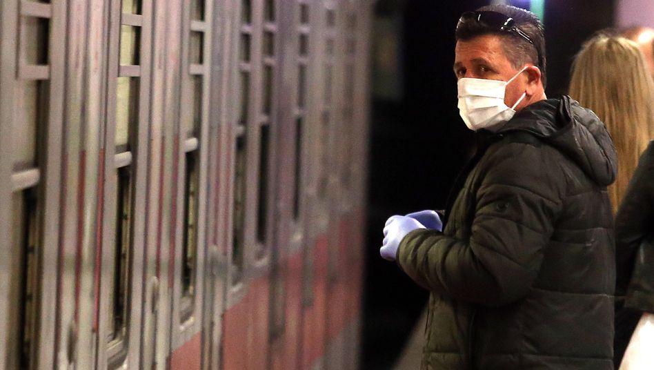 Ein Mann trägt in einer Mailänder Bahnstation Mundschutz