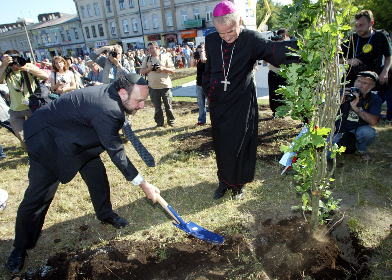 Chief Rabbi of Poland Michael Schudrich and Polish Bishop Marian Florczyk plant a tree next to a monument over the massacre of forty Polish Jews during the 60th anniversary in Kielce