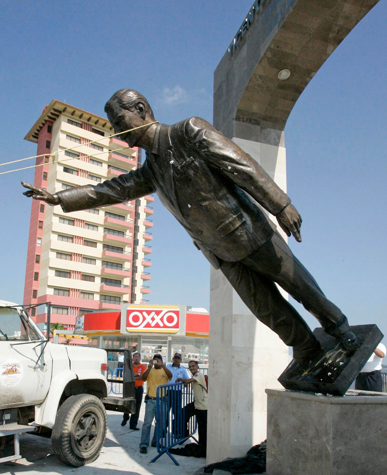 A statue of Mexico's former President Vicente Fox is seen as is knocked down by protesters in Boca del Rio, Mexico
