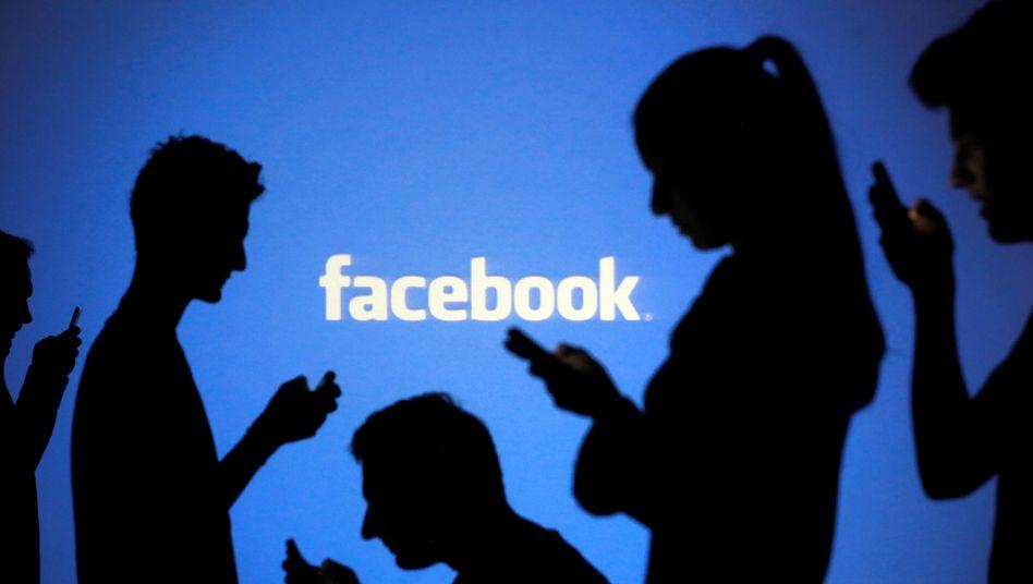 Smartphone-Nutzer vor Facebook-Schriftzug