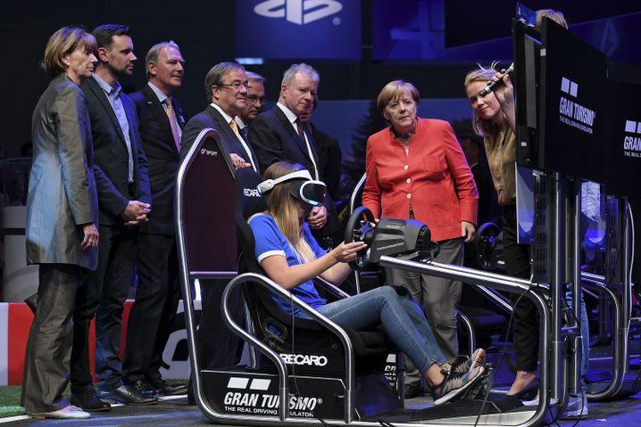Merkel neben Gamerin mit Virtual-Reality-Headset