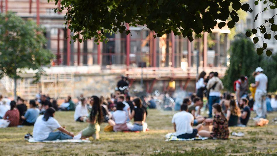 Menschen sitzen bei warmem Wetter im James-Simon-Park in Berlin