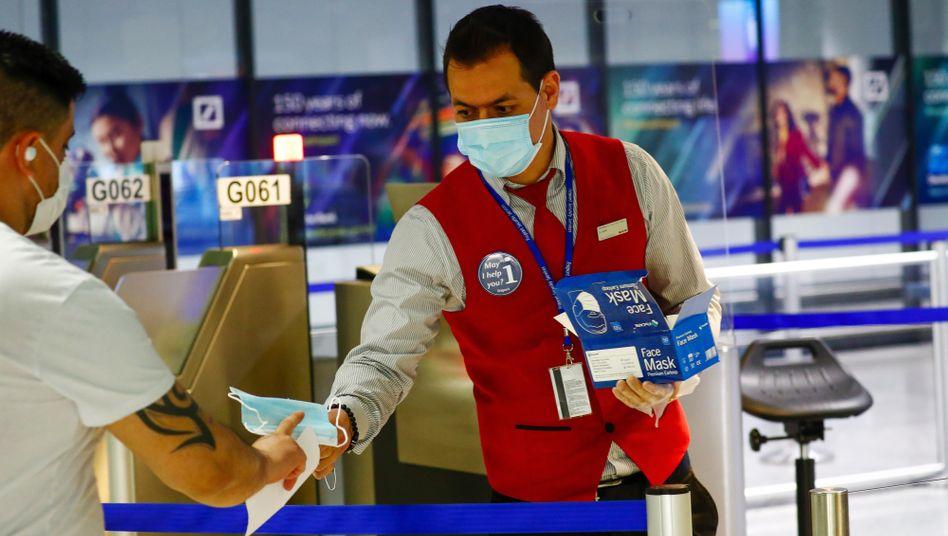 Am Flughafen Frankfurt teilt ein Mitarbeiter eine Schutzmaske an einen Fluggast aus