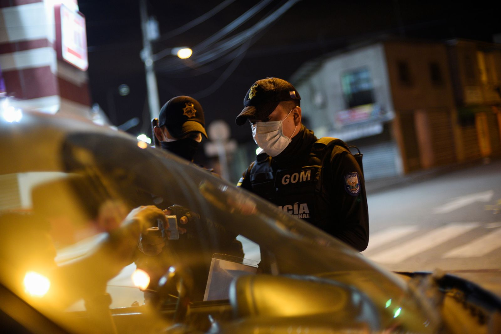Police officers stop a car at a checkpoint after Ecuador's government imposed a night curfew to prevent the spread of the coronavirus disease (COVID-19), in Guayaquil