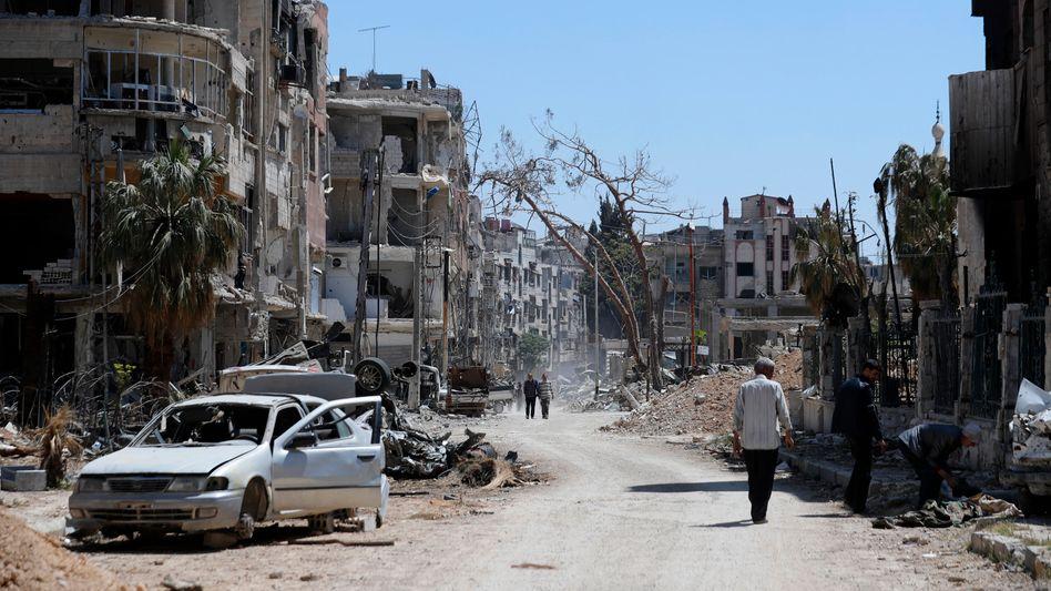Menschen vor zerstörten Häusern in Duma