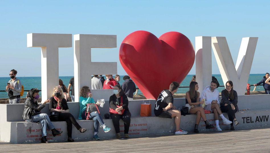 Coronalockerungen und erfolgreiche Impfkampagne in Israel: Menschen sitzen Tel Aviv vor der Küste des Mittelmeeres