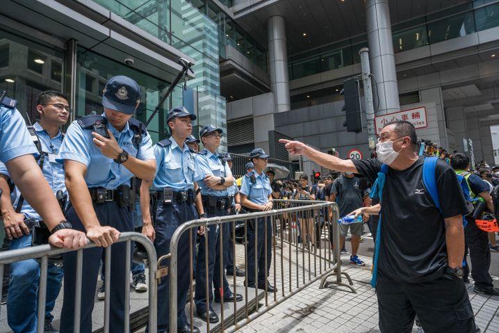 Ein Demonstrant vor einer Polizeisperre