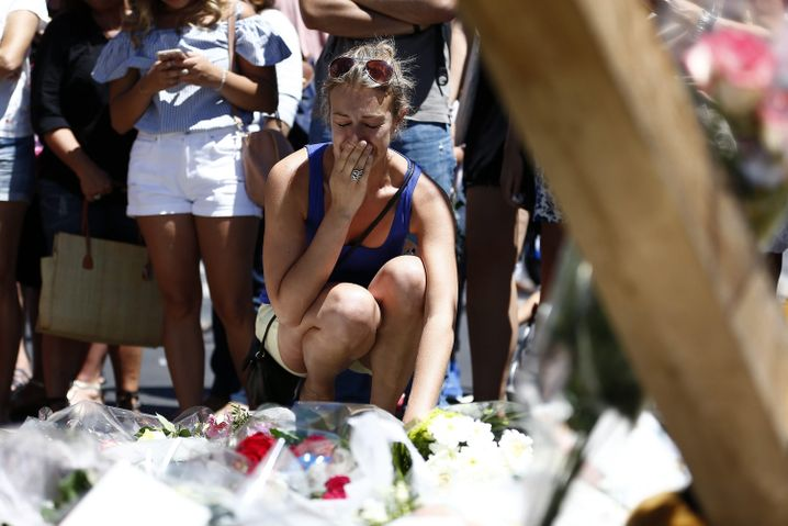 July 15, 2016: A woman mourns the dead in Nice after dozens were killed in a terrorist attack.