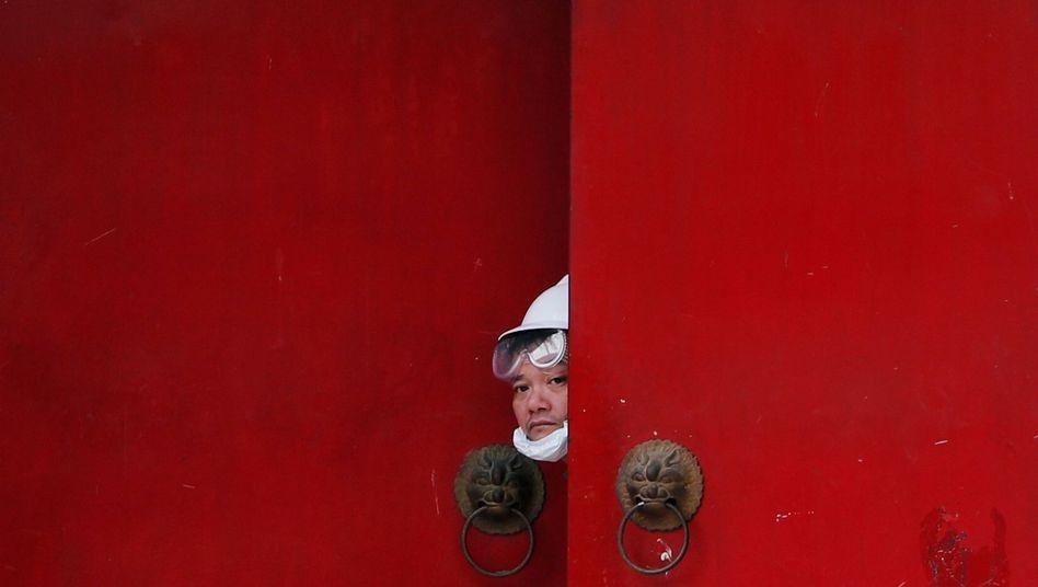 Ein Mann schaut während der Proteste in Hongkong aus einem Türspalt hervor: Neue Taktik