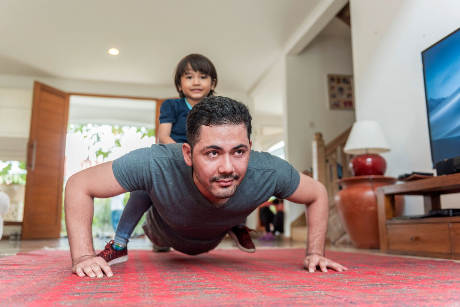 Father and son doing push up on a living room