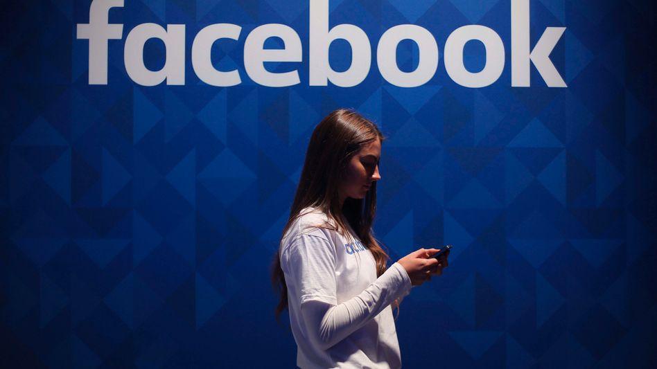 Eine junge Frau vor dem Facebook-Logo: Wie das »Wall Street Journal« herausfand, behandelte der Konzern nicht alle Nutzer gleich