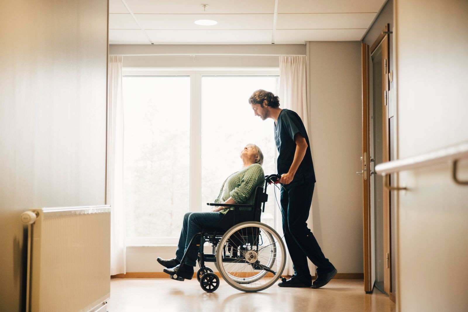 Full length side view of male nurse pushing disabled senior woman on wheelchair in alley at retirement home