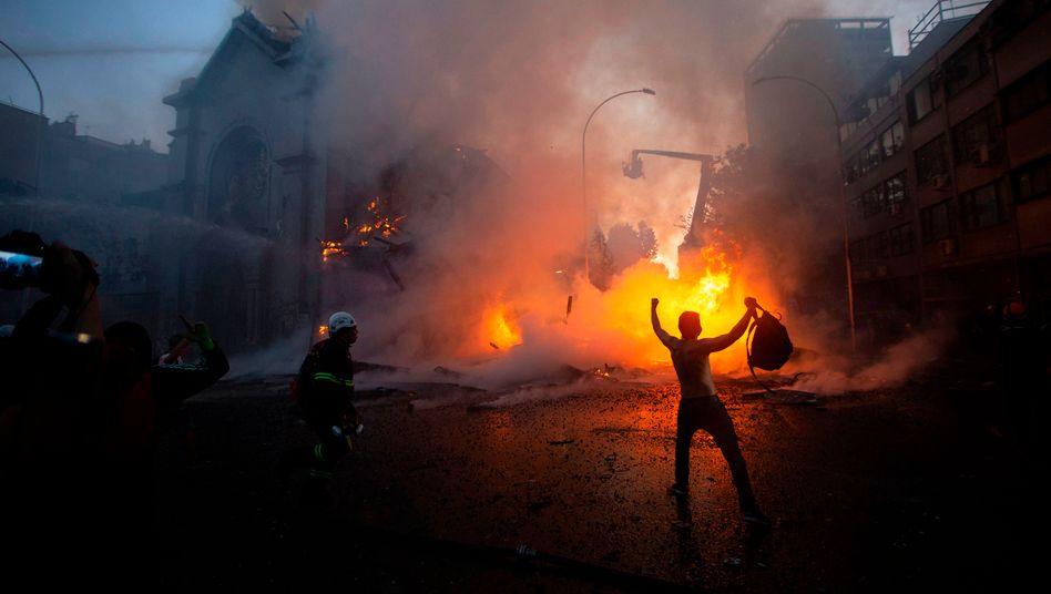 """Jubelnder Demonstrant vor brennender Kirche Iglesia de la Asunción in Santiago de Chile am vergangenen Sonntag: """"Rache für die Polizeigewalt"""""""