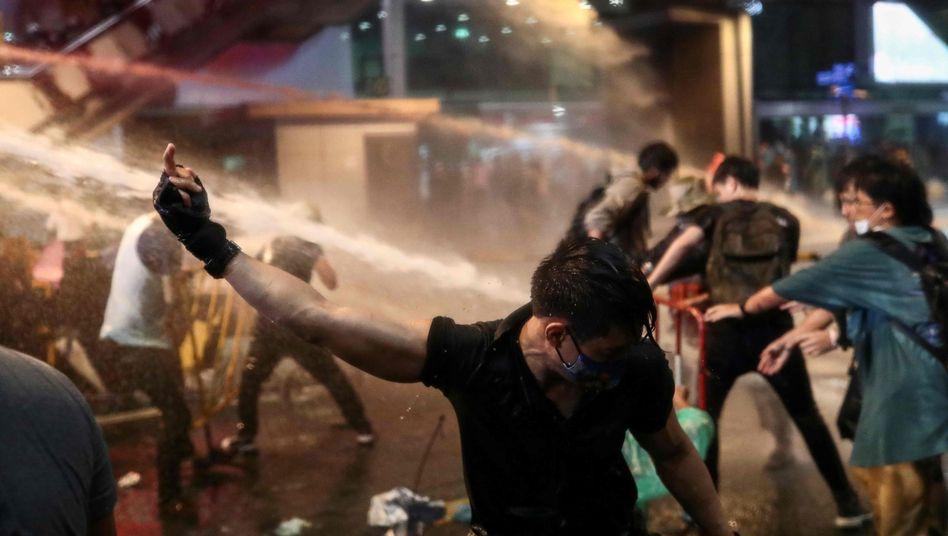 Ein Demonstrant zeigt am Freitag, dem 16. Oktober 2020, bei prodemokratischen Protesten in Bangkok, Thailand, den Wasserwerfern der Polizei den Mittelfinger