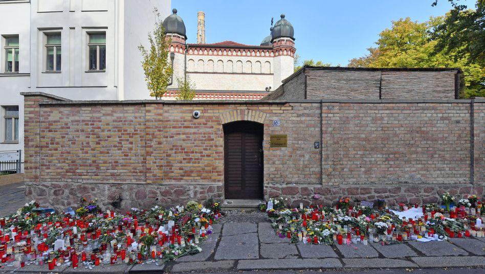 Halle (Saale): Blumen und Kerzen stehen neben der Tür zur Synagoge, vier Tage nach dem rechtsextremistischen Anschlag auf die Gemeinde