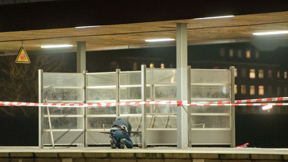 Ein Polizist untersucht den Tatort am S-Bahnhof Veddel