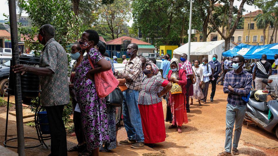 Menschen in Kampala stehen Schlange, um gegen Corona geimpft zu werden