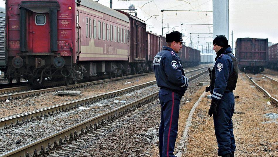 Von der Schiene auf die Straße: Polizisten bewachen den Güterzug mit Trümmern von Flug MH17 in Charkiw