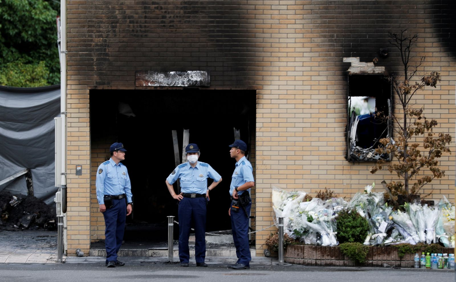 FILE PHOTO: Policemen are seen at the torched Kyoto Animation building in Kyoto